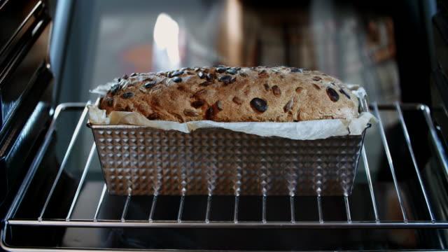 vídeos de stock e filmes b-roll de baking homemade seed bread in the oven - fazer doces