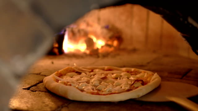 CU baking pizza in brick oven