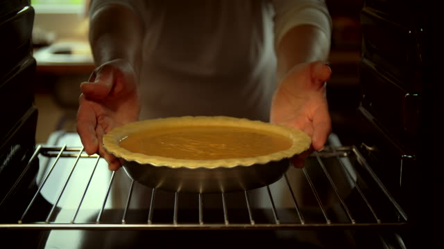 baking pumpkin pie for the holidays in the oven - 4k video - pastry dough stock videos & royalty-free footage