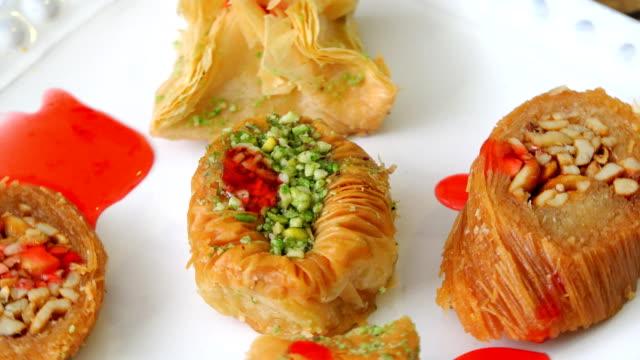 バクラヴァスイーツ各種。pastrie カバー、ピスタチオナッツおよびナット付き - ピスタチオナッツ点の映像素材/bロール