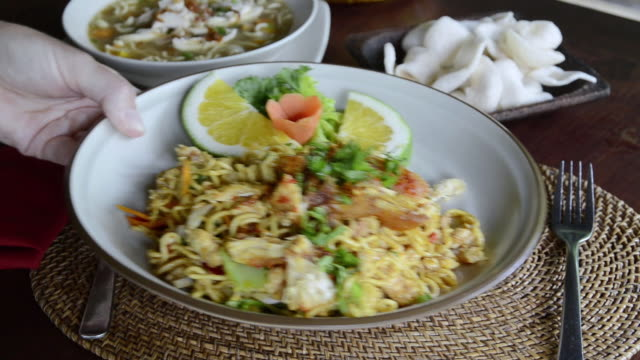 vidéos et rushes de cu bakmi goreng being serve with fried noodle, chicken, egg, kerupuk crackers, noodle soup, pinapple juice and balinese food at asia / ubud, bali, indonesia - assiette