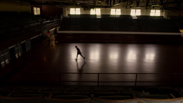 a baksetball player practices three point shots in an empty gymnasium. - sporthalle stock-videos und b-roll-filmmaterial