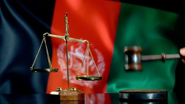 balance und gavel mit afghani-flagge - afghanische flagge stock-videos und b-roll-filmmaterial