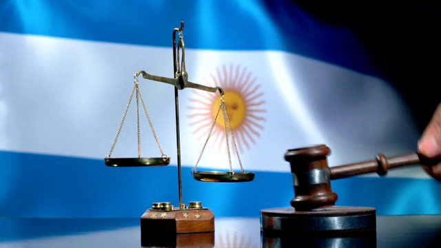 balance und gavel mit argentinischer flagge - argentinische flagge stock-videos und b-roll-filmmaterial