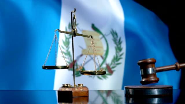 stockvideo's en b-roll-footage met balans en hamer met guatemalteekse vlag - oordeel juridische procedure