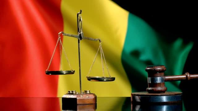 vidéos et rushes de équilibre et gavel avec le drapeau guinéen - social justice concept