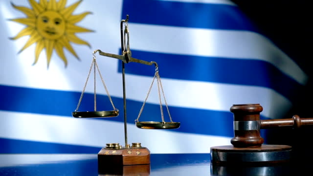 balance and gavel with uruguaian flag - uruguaian flag stock videos & royalty-free footage