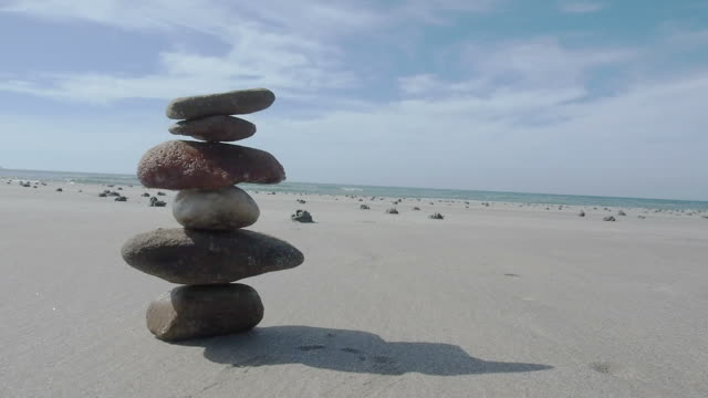 balance stone on the beach - stone object stock videos and b-roll footage