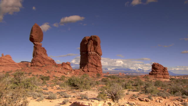 balanced rock with bright blue skies - zoom in from wide shot - arches national park stock videos & royalty-free footage