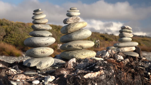 vidéos et rushes de pierres équilibrées sur une plage de galets. - sans mise au point and équilibre