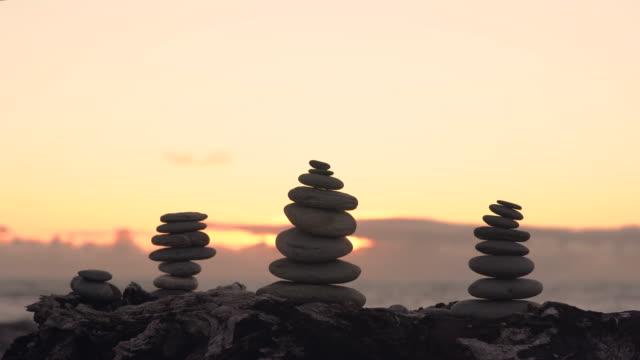vidéos et rushes de pierres équilibrées sur une plage de galets avec le coucher du soleil à l'arrière-plan. - sans mise au point and équilibre