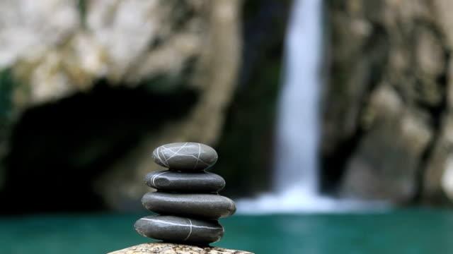 Balanced stones on waterfall background