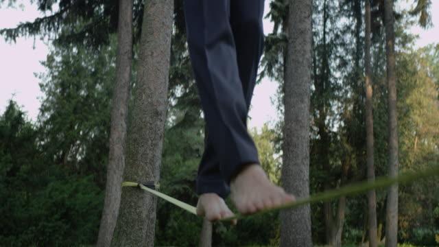vidéos et rushes de équilibrant pieds nus sur une slackline. formation d'homme d'affaires - stabilité
