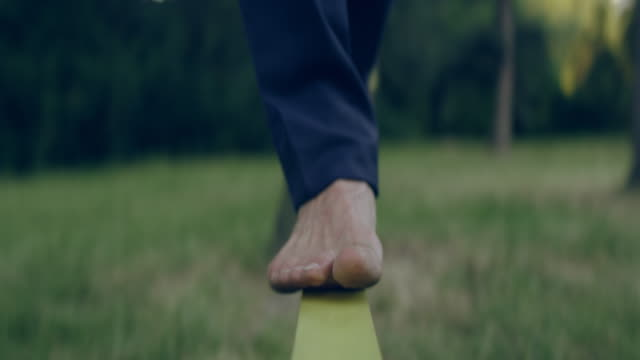 balancing barefoot on a slackline. businessman training - balance stock videos & royalty-free footage