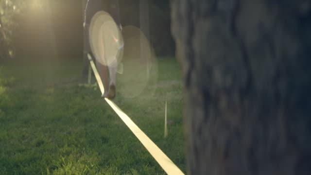 balancing barefoot on a slackline. summer afternoon in park - freizeit stock-videos und b-roll-filmmaterial