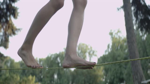 vídeos de stock e filmes b-roll de balancing barefoot on a slackline. summer afternoon in park - corda
