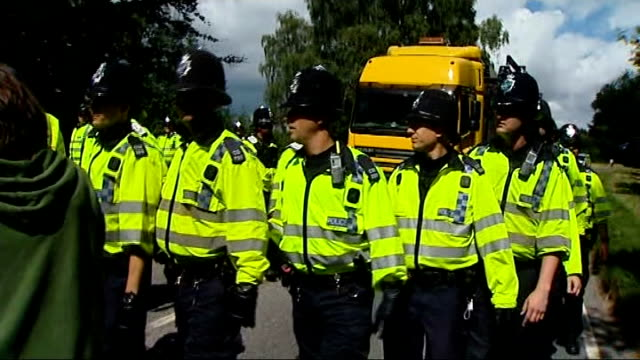 Balcombe fracking protests continue ENGLAND Sussex Balcombe EXT People along at protesters camp / 'No more dirty energy' banner / police officers and...