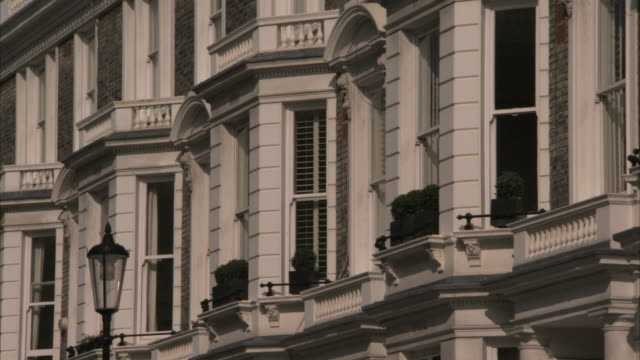 Balconies and bay windows decorate the facade of a mansion flat. Available in HD.