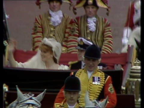 balcony kiss; : england: london: outside abbey as couple wave to crowds: couple along in open carriage as sarah gives thumbs up sign: edward with... - itv news at ten点の映像素材/bロール