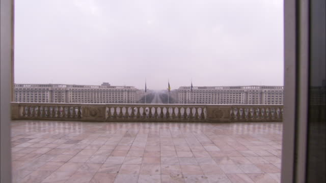 A balcony on the front of the Palace of Parliament overlooks government buildings and a long, central straight road. Available in HD