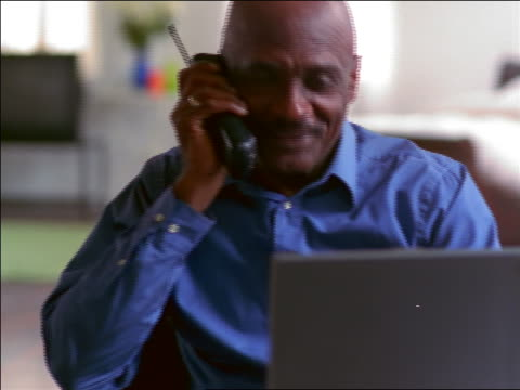 bald black man sitting in front of laptop computer talking on cordless phone - einzelner mann über 40 stock-videos und b-roll-filmmaterial