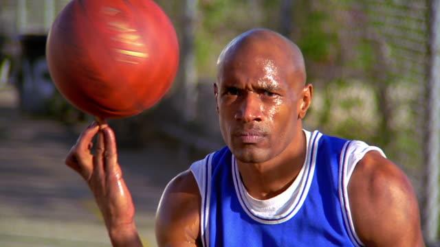 vidéos et rushes de ms portrait bald black man sitting spinning basketball on his finger + smiling outdoors /los angeles - tournoyer