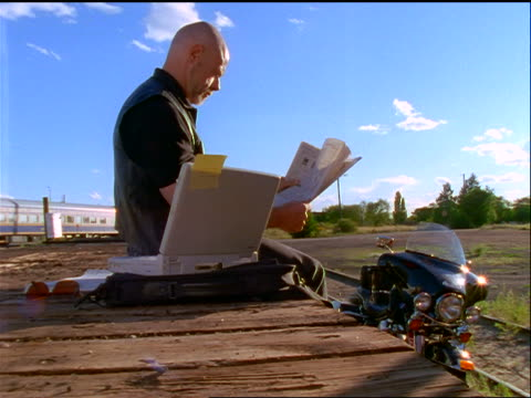 bald man in black sitting in train yard reading newspaper with laptop + motorcycle next to him - completely bald stock videos and b-roll footage