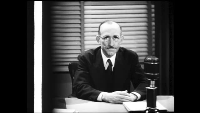 bald man in suit talking to the microphone sitting behind an office desk; sound strip on the left side as he speaks - 1940 1949 stock videos & royalty-free footage