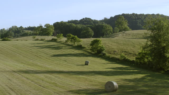 WS AERIAL POV Bale on rural landscape with tree area / Smyth County, Virginia, United States
