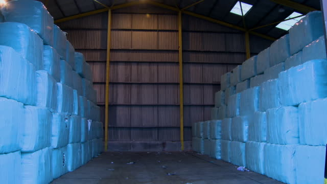 bales destined for incineration in a warehouse - hay bail stock videos & royalty-free footage