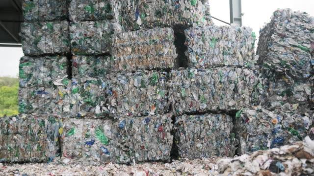 vídeos y material grabado en eventos de stock de bales de materiales reciclables comprimidos apilados al aire libre - embalaje