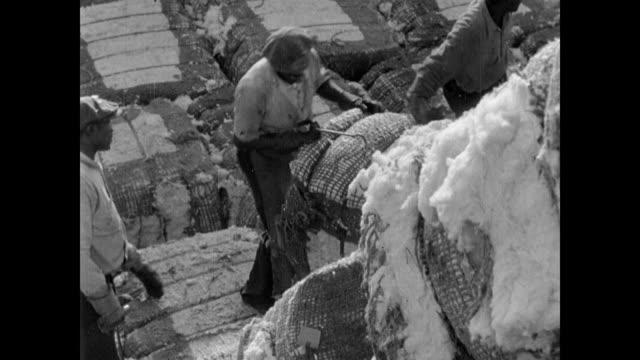 vídeos y material grabado en eventos de stock de / bales of cotton being loaded onto a ship / cotton being spun / huge pile of bales being loaded cotton bales loaded onto ship during the great... - 1937