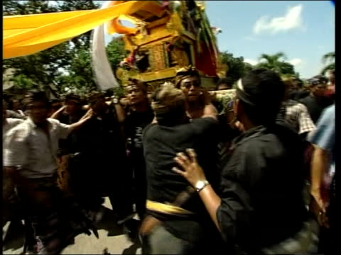 police investigation; indonesia: bali: kuta: ext mourners carry elaborate coffinalong road at funeral of i gusti sudana, one of victims of bombings... - mourner stock videos & royalty-free footage