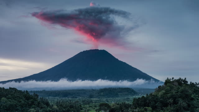 bali, timelapse of mount agung volcano discharging volcanic ash during eruptive stage - eruzione video stock e b–roll