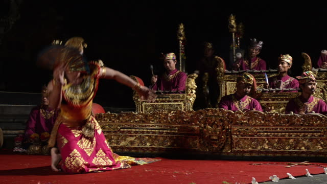 vídeos de stock e filmes b-roll de ms ts balinese dancer is performing kebyar terompong dance in front of gamelan orchestra in puri saraswati temple audio / ubud, bali, indonesia, asia - gamelão