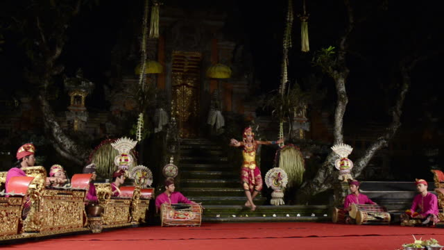 vídeos de stock e filmes b-roll de ms balinese dancer performing fisherman dance in front of gamelan orchestra in puri saraswati temple audio / ubud, bali, indonesia - gamelão