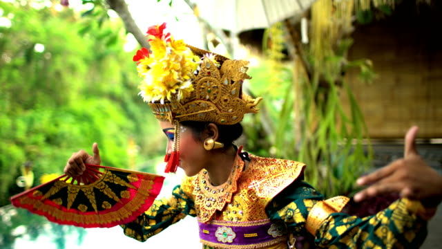 Balinese female artistic dancer performing in ceremonial costume