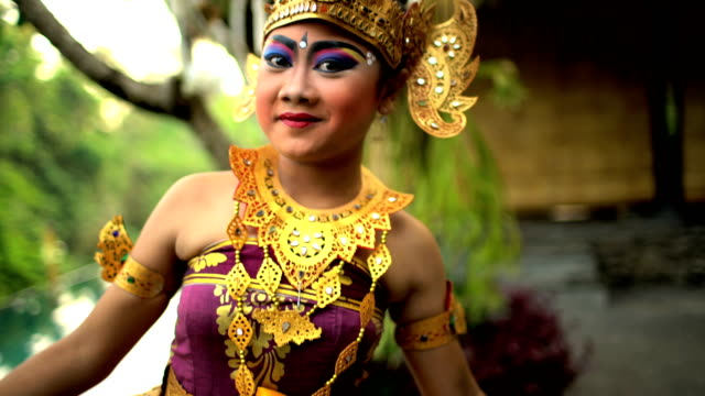 Balinese female artistic dancer performing in colorful costume