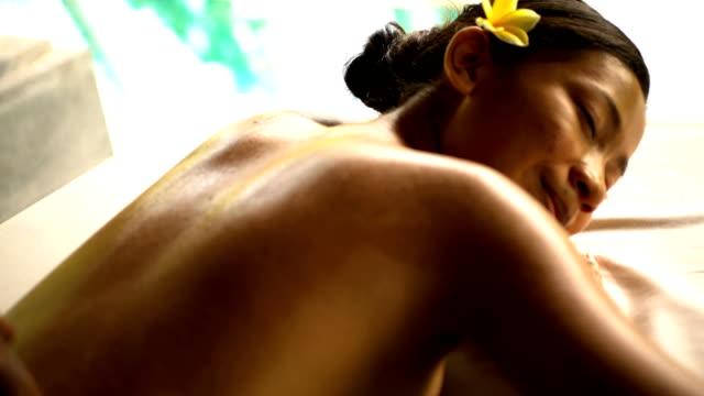 balinese female at spa with hot stone massage - spa treatment点の映像素材/bロール