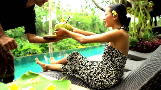 balinese female enjoying coconut juice by pool indonesia - パレオ点の映像素材/bロール