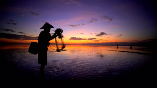 balinese fisherman throwing net into indian ocean sunset - headwear stock videos & royalty-free footage