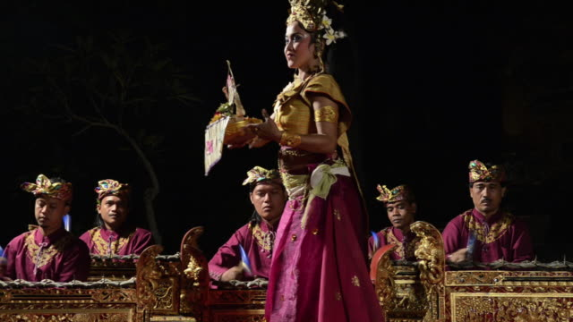 vídeos de stock e filmes b-roll de ms balinese girl dancer are performing tari penyambutan dance ( goddess of moon ) in front of gamelan orchestra in puri saraswati temple audio / ubud, bali, indonesia, asia - gamelão