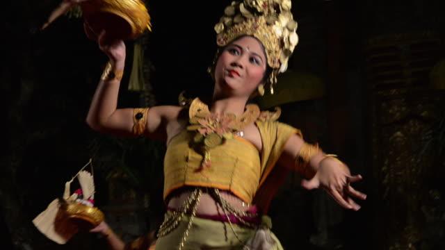 MS Balinese girl dancer are performing Tari Penyambutan Dance ( Goddess of Moon ) in front of Gamelan Orchestra in Puri Saraswati temple AUDIO / Ubud, Bali, Indonesia, Asia