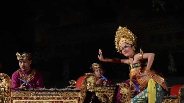 vídeos de stock e filmes b-roll de ms pan balinese girl dancer is performing oleg tamulilingan dance ( love story ) in puri saraswati temple audio / ubud, bali, indonesia, asia - gamelão