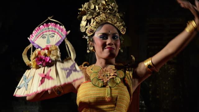 vidéos et rushes de ms balinese girl dancer is performing tari penyambutan dance ( goddess of moon ) in puri saraswati temple audio / ubud, bali, indonesia, asia - coiffe traditionnelle