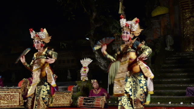 vídeos de stock e filmes b-roll de ms balinese girl dancers performing legong dance in front of gamelan orchestra in puri saraswati temple audio / ubud, bali, indonesia - gamelão