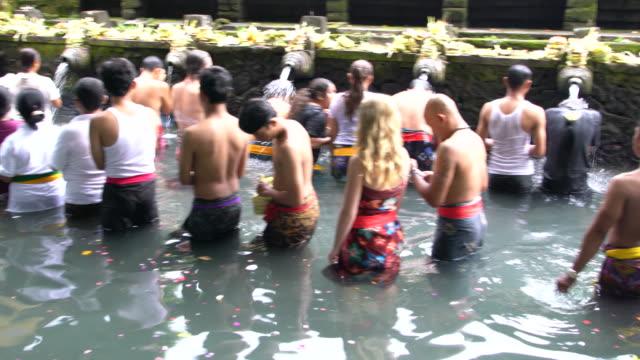 balinese hindus go to for ritual purification at pura tirta empul temple, bali - acqua santa video stock e b–roll
