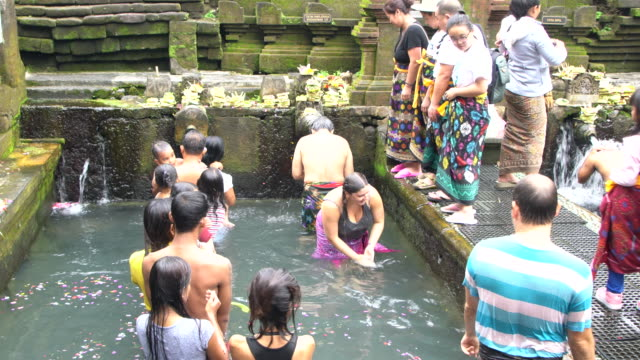 balinese hindus go to for ritual purification at pura tirta empul temple, bali - sarong stock-videos und b-roll-filmmaterial