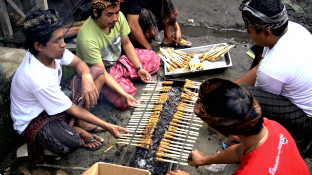 balinese males cooking satay kebabs on open fire - indonesia street stock videos & royalty-free footage