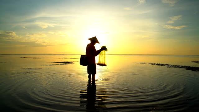 balinese man casting fishing net on indonesian coastline - 男漁師点の映像素材/bロール
